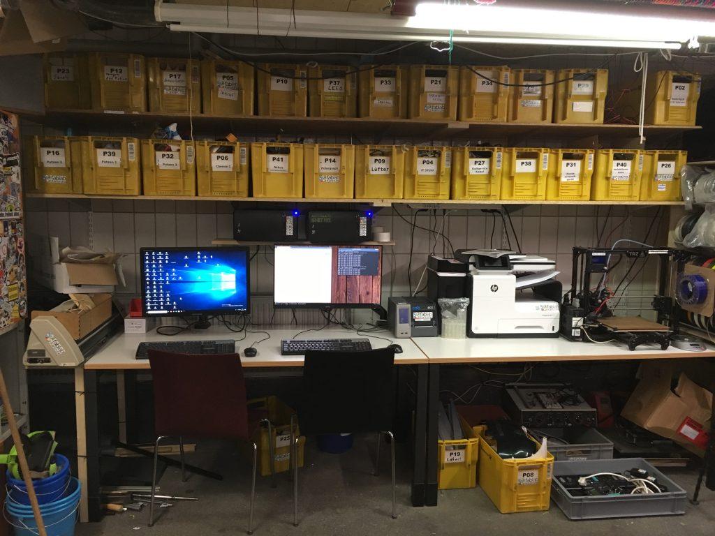 Computertische mit darüber liegenden Materialregalen